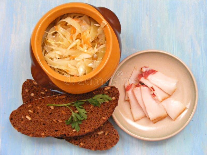 Kokkonst av Vitryssland, traditionell rysskokkonstsurkål i en keramisk trummakruka med avbrottet på blå sjaskig bakgrund arkivfoton