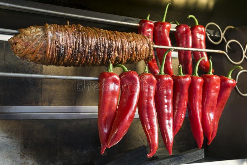 Kokorec e certas pimentas vermelhas doces em um espeto imagens de stock
