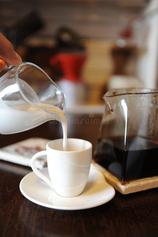 Kokosmelk in een kop van zwarte koffie wordt gegoten die r stock foto's