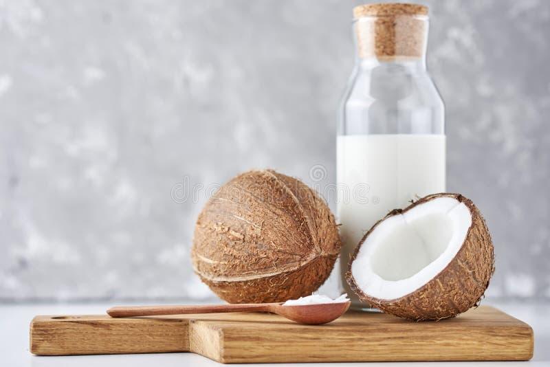 Kokosmelk in glasfles en verse kokosnoten met de helft op een grijze achtergrond stock afbeelding