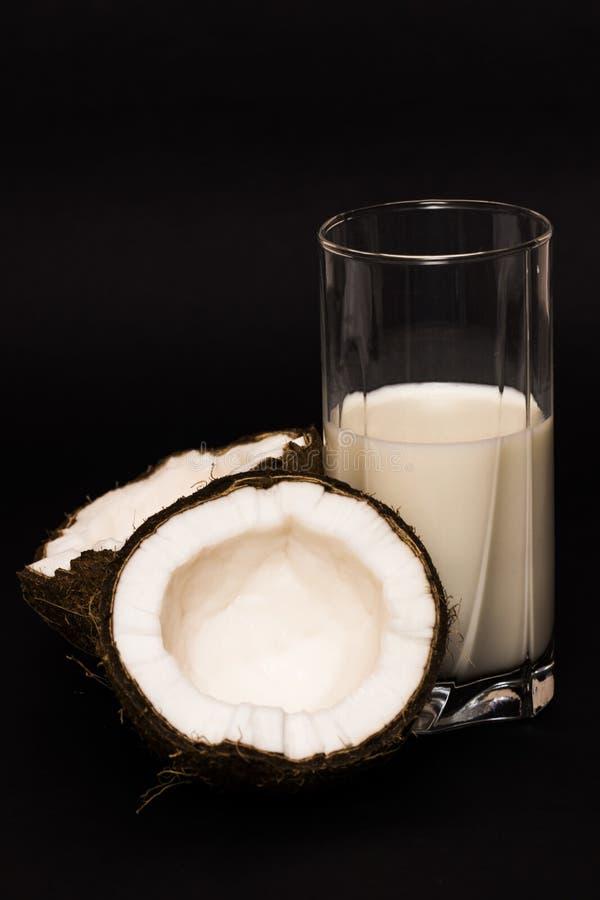 Kokosmilch und Kokosnuss auf schwarzem Hintergrund stockbild