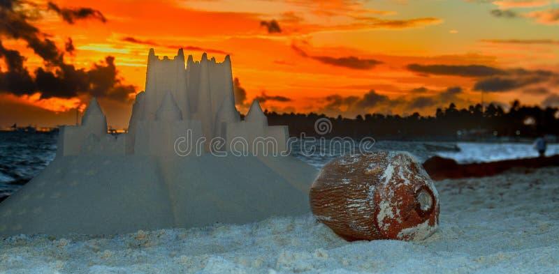 Kokosnöt på stranden med en sandslott, blått hav royaltyfria foton