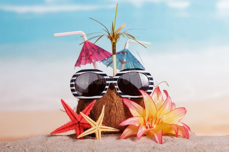 Kokosnöt, solglasögon, sjöstjärna och blomma i sanden mot havet arkivbilder