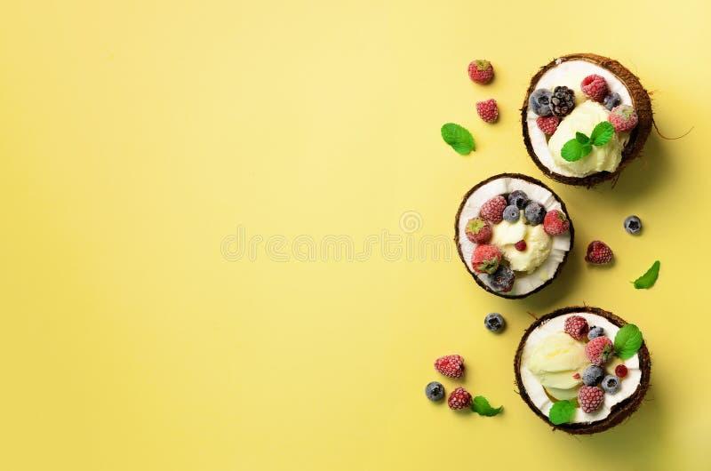 Kokosnötglass med nya bär i kokosnöthalvor på gul bakgrund med kopieringsutrymme Top beskådar Beståndsdelar för website eller pre royaltyfria foton