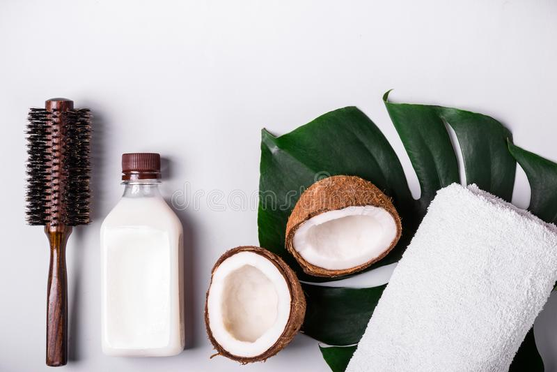 Kokosnötolja och tropiska sidor Begrepp för brunnsort för håromsorg royaltyfria bilder