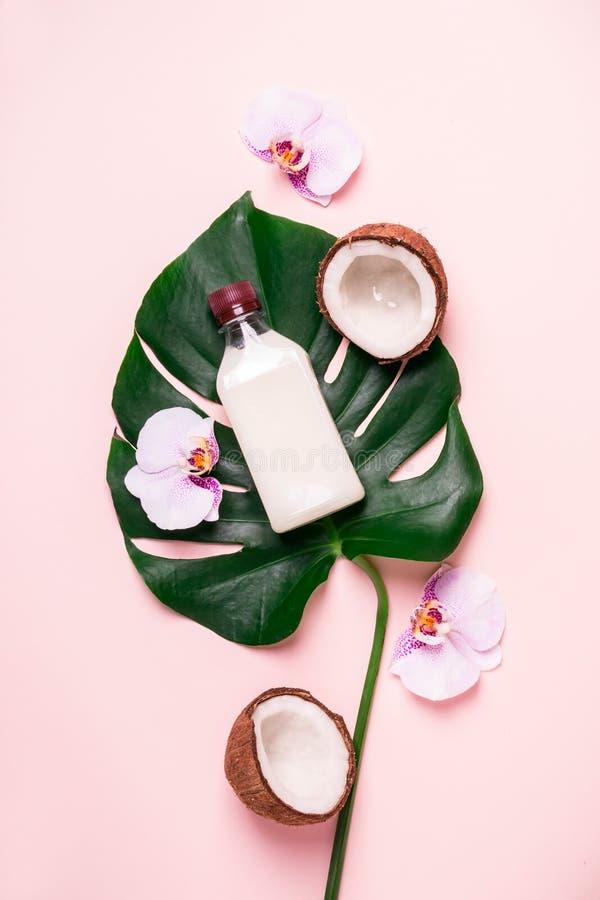 Kokosnötolja och tropiska sidor och blommor Begrepp för brunnsort för håromsorg royaltyfri fotografi