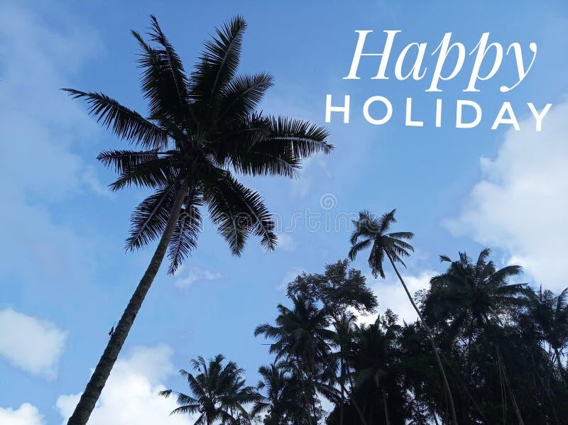 Kokosnötpalmträd och den blåa himlen med lycklig ferietext royaltyfria bilder