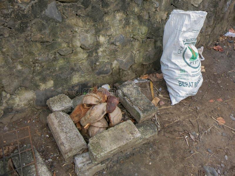 Kokosnötskal i spisen Förbereda sig för att grilla för kött Primitivt galler i Indonesien Tegelstenar stenar, trådingrepp royaltyfri fotografi