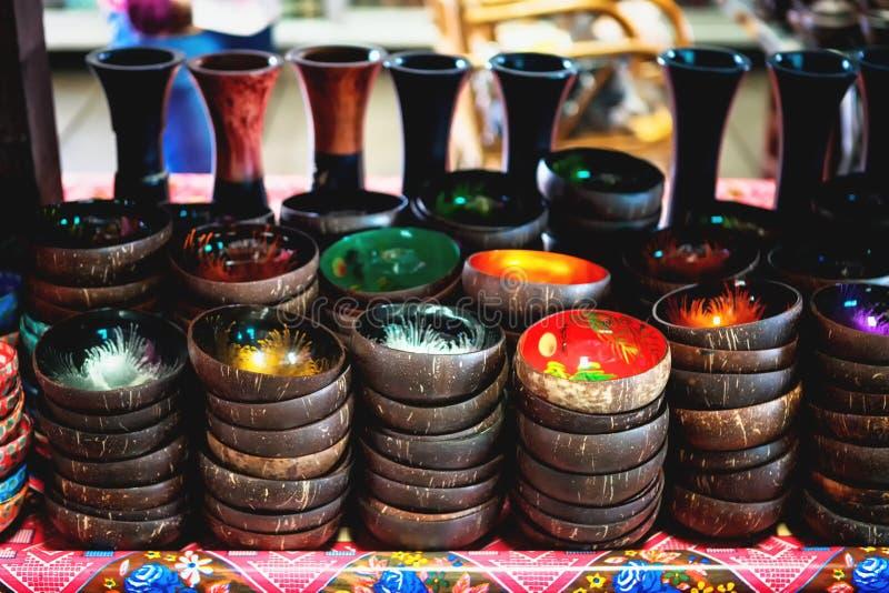 Kokosnötskalbunkar på trähyllan Souvenirkokosnötbunkar som säljer på marknaden fotografering för bildbyråer