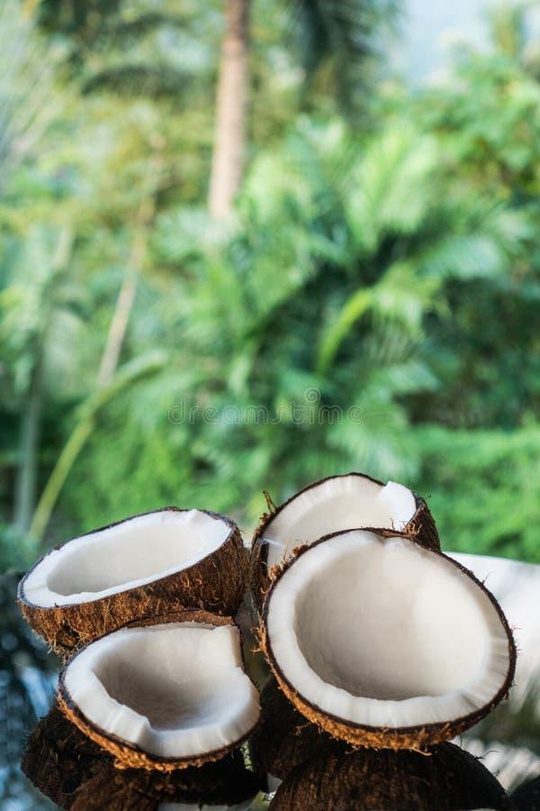 Kokosnüsse auf dem schwarzen Glastisch lokalisiert über unscharfem Palmehintergrund stockfotografie