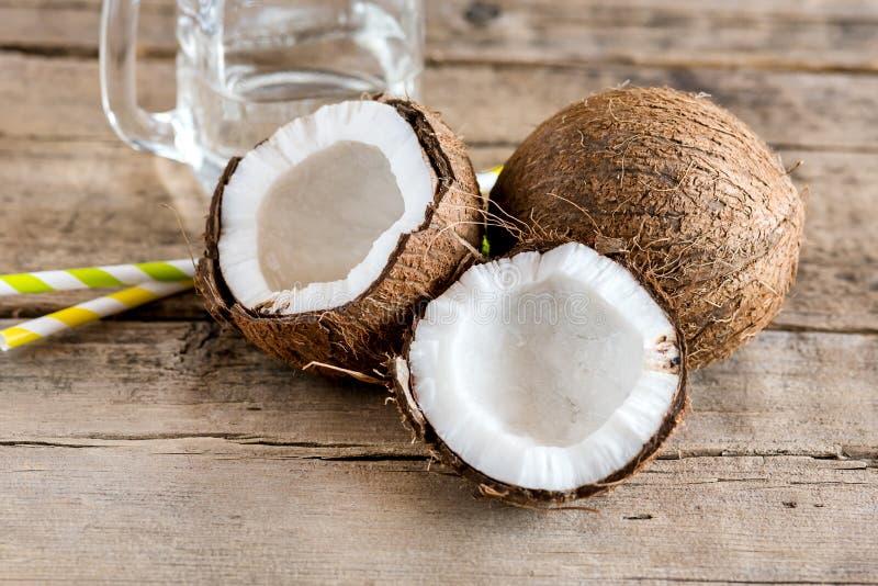 Kokosnüsse und Glasgefäß mit Kokosnuss-Wasser-altem hölzernem Hintergrund Straw Horizontal stockbild