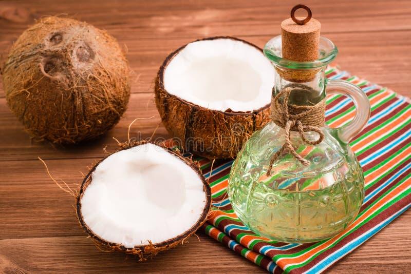 Kokosnüsse und Kokosnussöl in einer Flasche stockbild