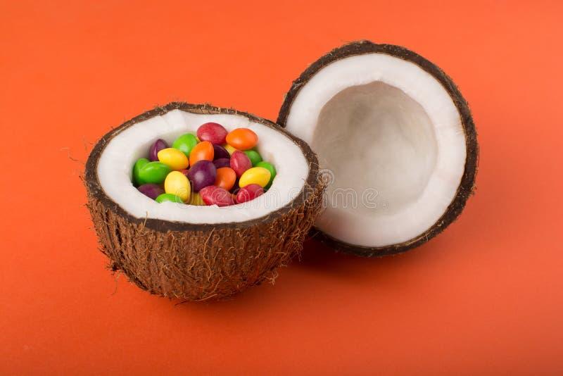 Kokosn?t med f?rgrika godisar arkivfoto
