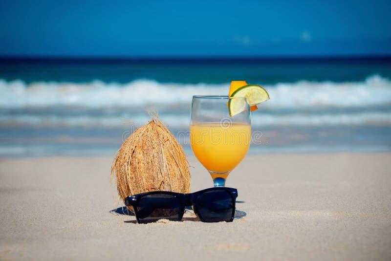 Kokosnoot, cocktail en glazen door de oceaan stock foto