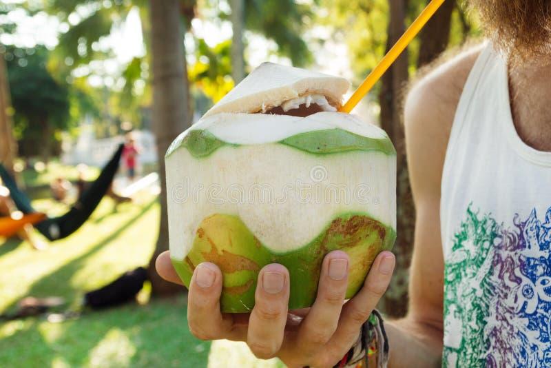 Kokosnoot met sap en oranje stro in een hand van de mens op een achtergrond van park met palmen stock fotografie