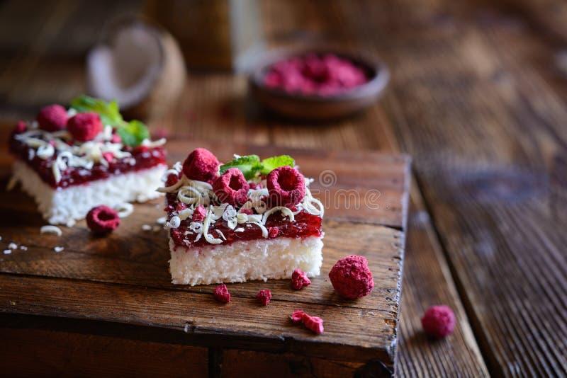 Kokosnotencake met frambozenlaag en bedekt met witte chocoladespaanders en vorst - droge frambozen stock fotografie
