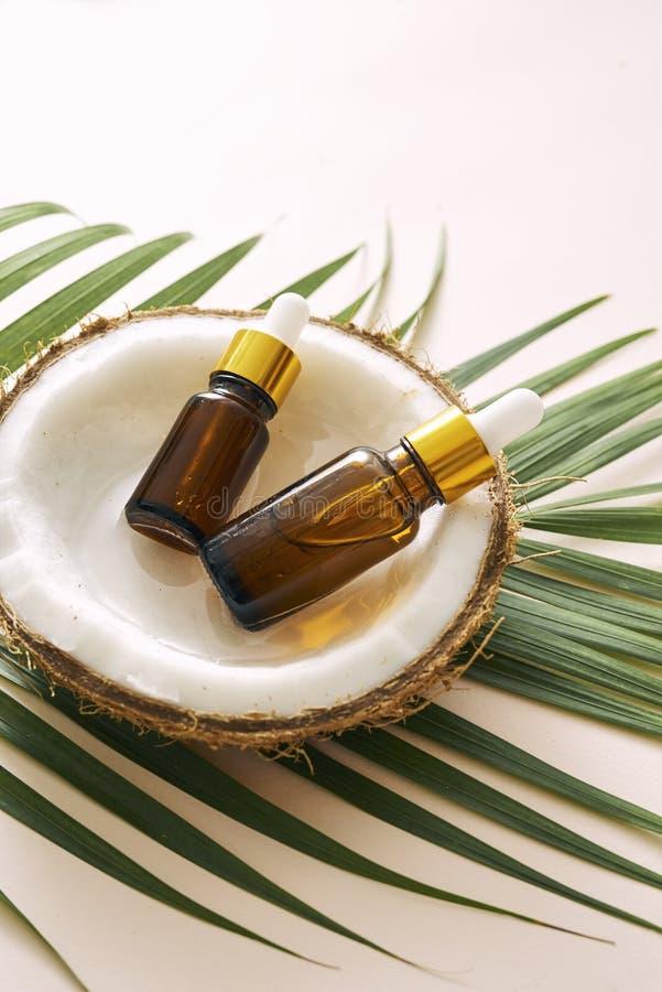 Kokosnotenolie in fles met open noten en pulp in kruik, groene palmbladachtergrond Natuurlijke cosmetischee producten royalty-vrije stock fotografie