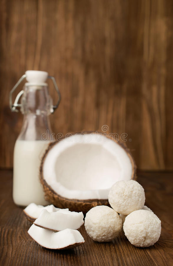 Kokosnuss, Milch in einer Glasflasche und Süßigkeiten lizenzfreie stockfotos