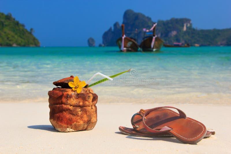 Kokosnusscocktail und -Sandalen auf dem Strand stockfotografie