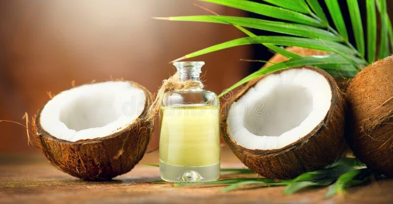 KokosnussPalmöl in einer Flasche mit Kokosnüssen und grünem Palmeblatt auf braunem Hintergrund Coconussnahaufnahme Gesunde Nahrun stockfoto