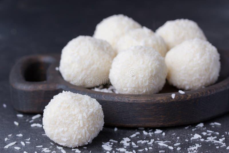 Kokosnusssüßigkeit auf einem hölzernen Brett Runde Kokosnussbälle lizenzfreie stockfotografie