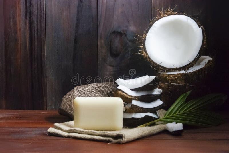 Kokosnussseife mit Kokosnusshälfte und Kokosnussstücke und -blatt auf Holztisch lizenzfreie stockbilder