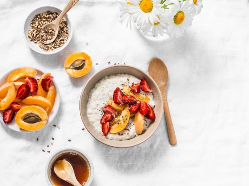 Kokosowego mleka oatmeal owsianka z truskawek, morel, miodu i lna ziarnami, Wyśmienicie zdrowy śniadanie na lekkim tle zdjęcia stock