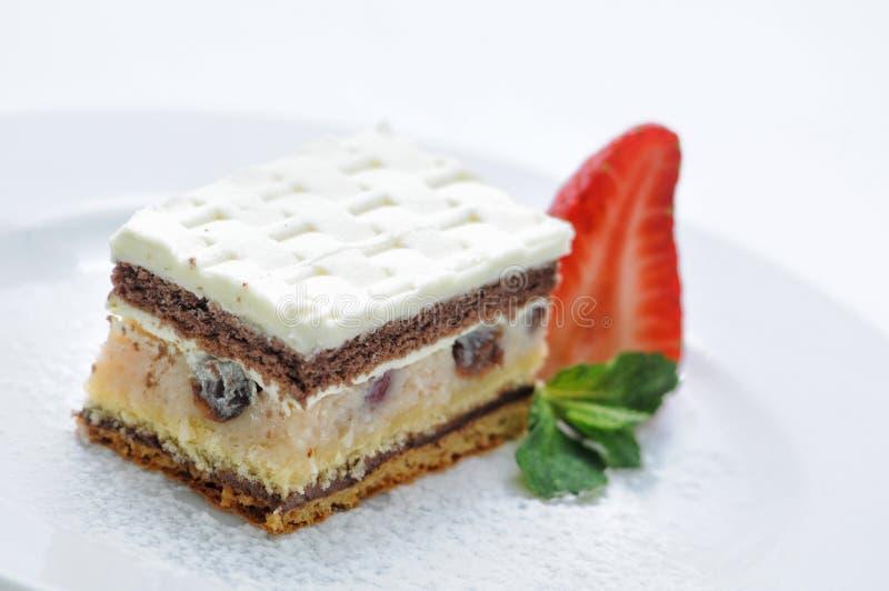 Kokosowy tort z marcepanami i truskawką na bielu talerzu, fotografia dla sklepu, patisserie obraz stock