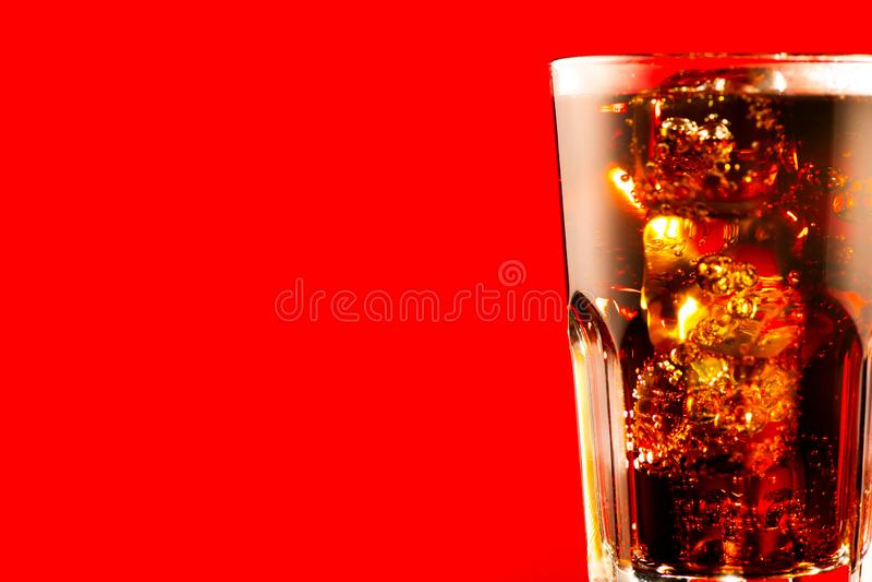 Koks mit Eiswürfelnahaufnahme Glas des sprudelnden braunen Getränks über Rot lizenzfreie stockbilder