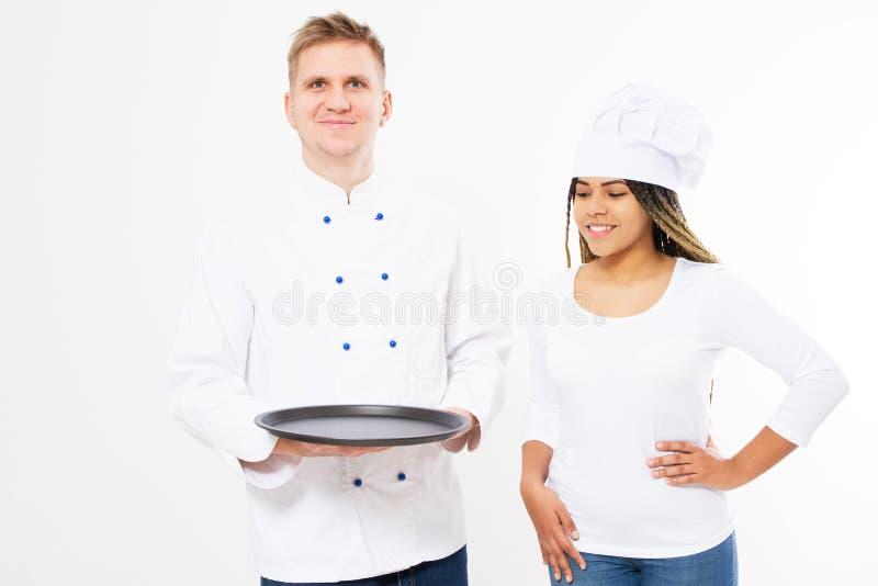 Koks van glimlach houden de zwarte vrouwelijke en witte mannelijke chef-koks een leeg die dienblad op witte achtergrond wordt geï stock foto's