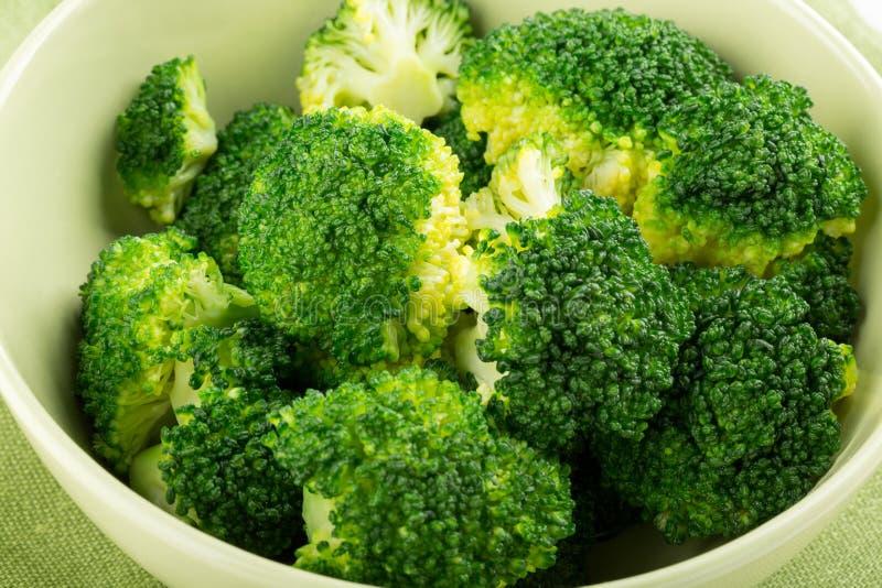 Kokt broccoli i grön bunke arkivbild