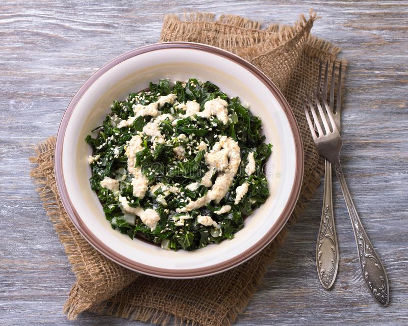 Kokt grönkål med tahinisås- och sesamfrö royaltyfria bilder