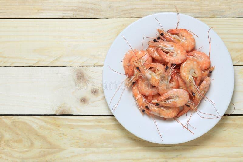 Kokt havsräka i den vita maträtten på trägolv royaltyfria foton