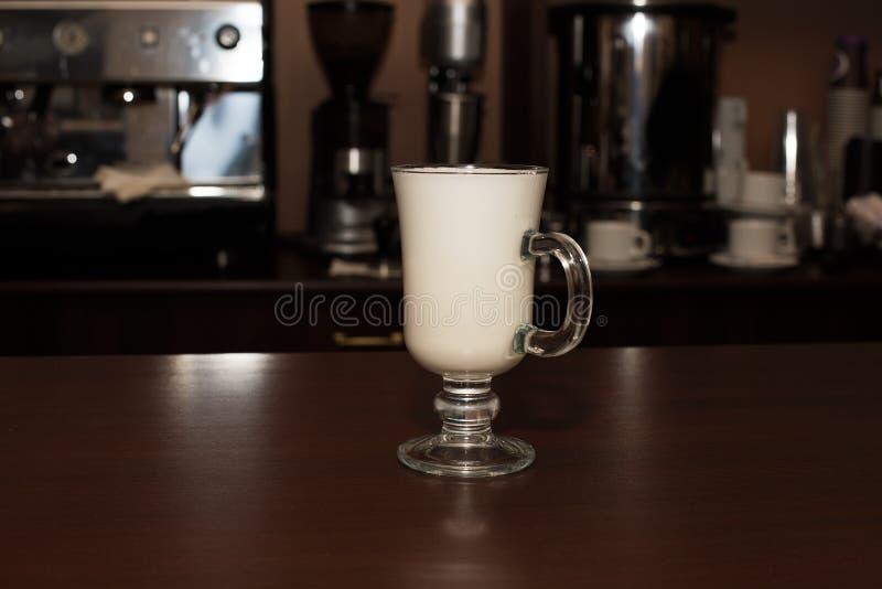 Kokt mjölka i ett genomskinligt exponeringsglas på en kaféräknare arkivbild