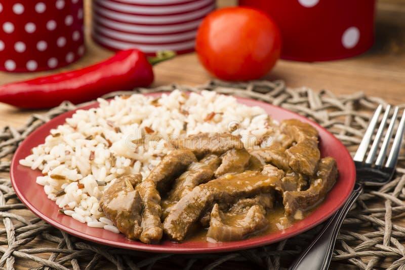 Kokt nötkött och ris på den röda plattan arkivfoton