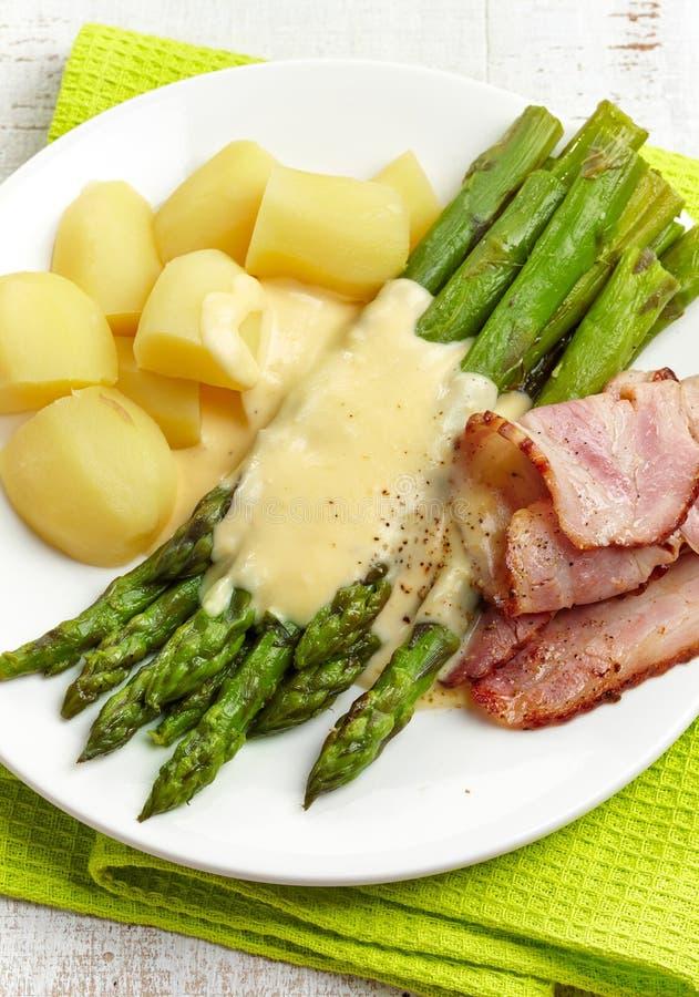Kokt sparris, potatisar, bacon och hollandssås arkivfoto