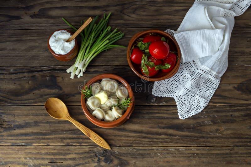Kokta klimpar i en bunke, en gräddfil och en inlagd kokkonst för ryss för närbild för tomater ukrainsk och royaltyfri fotografi