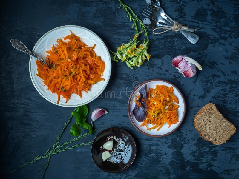 Kokta morötter med vitlök och persilja på ljusa plattor på en mörk bakgrund arkivfoton