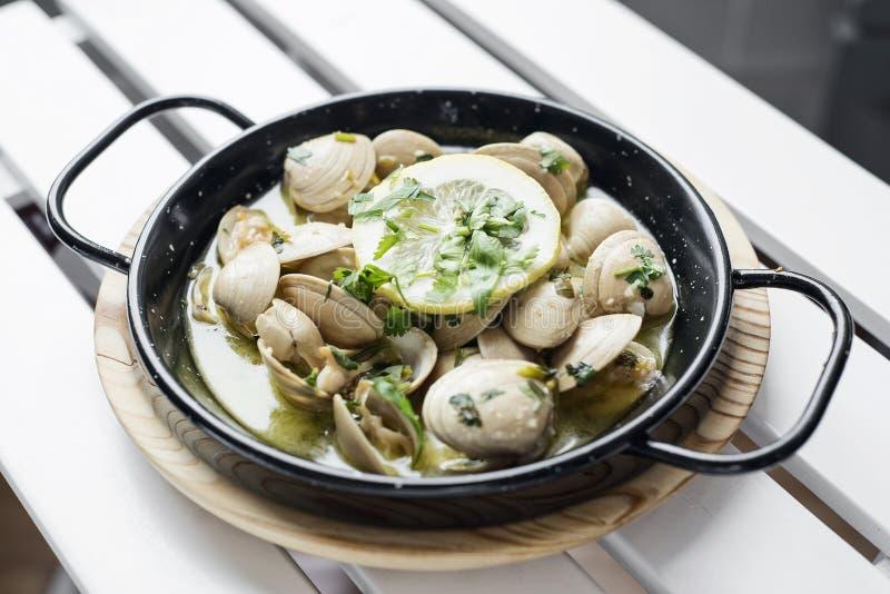 Kokta musslor i vitlökört och havs- sås för vitt vin royaltyfria bilder