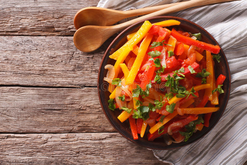 Kokta peppar med tomater och lökar stänger sig upp horisontalöverkant royaltyfri bild