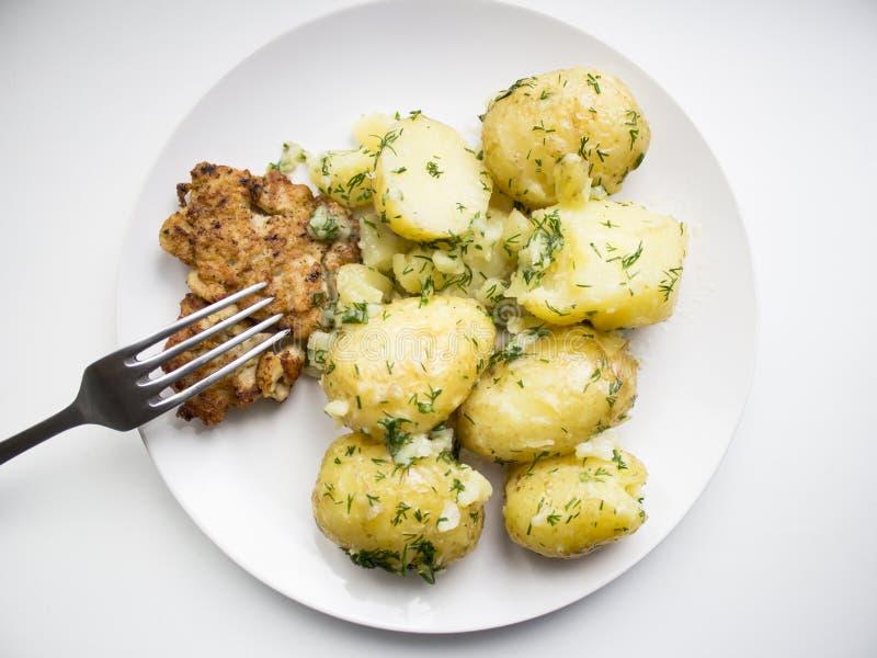 Kokta potatisar med persilja- och hönabiff royaltyfria bilder