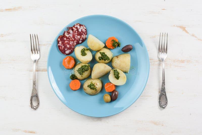 Kokta potatisar, morötter och salami tjänade som på plana turkosplommoner arkivfoto