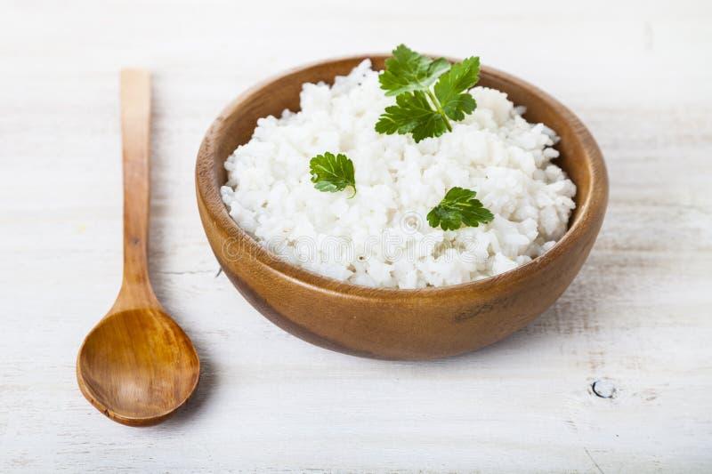 Kokta ris i en träbunke och sked royaltyfria foton