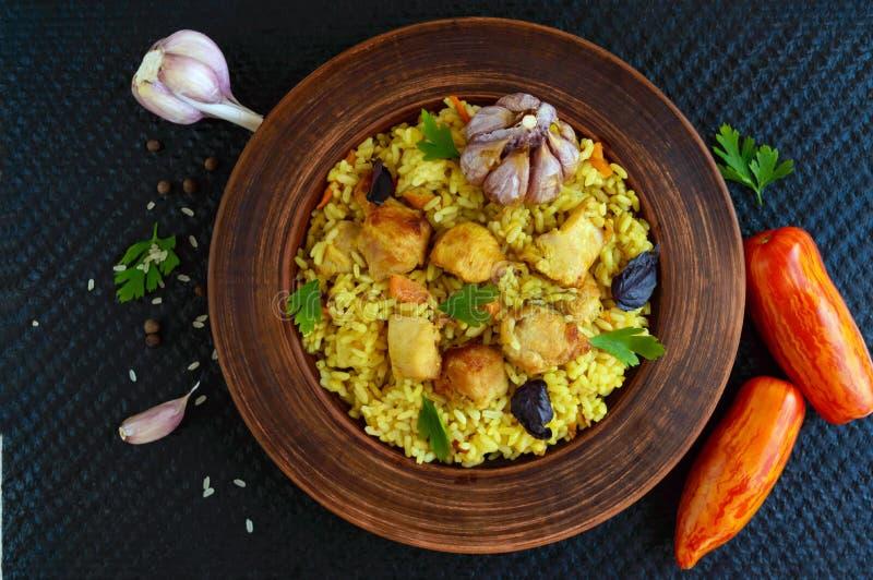 Kokta ris med grillad höna, morötter, kryddor (den traditionella asiatiska maträtten - pilaff) royaltyfri bild