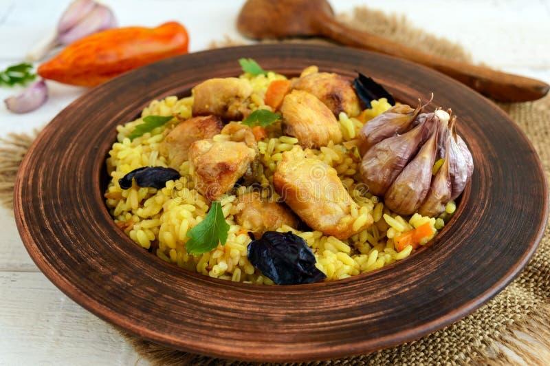 Kokta ris med grillad höna, morötter, kryddor (den traditionella asiatiska maträtten - pilaff) arkivfoto