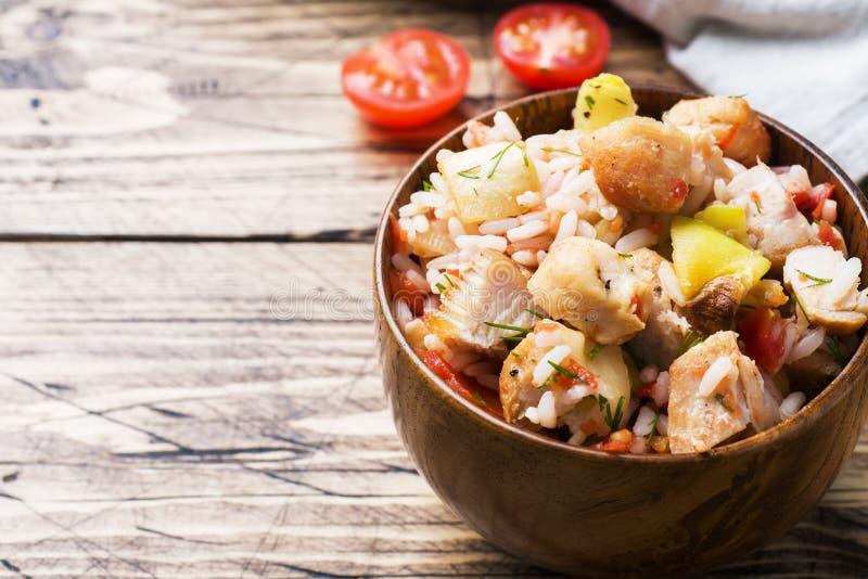 Kokta ris med höna och grönsaker i en träbunke royaltyfria bilder