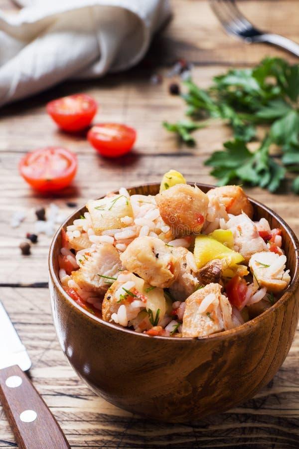 Kokta ris med höna och grönsaker i en träbunke royaltyfri bild