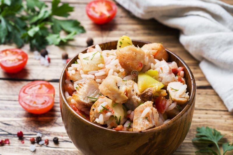 Kokta ris med höna och grönsaker i en träbunke royaltyfri fotografi