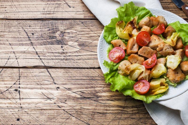 Kokta stycken av höna med grönsaker på en platta fotografering för bildbyråer