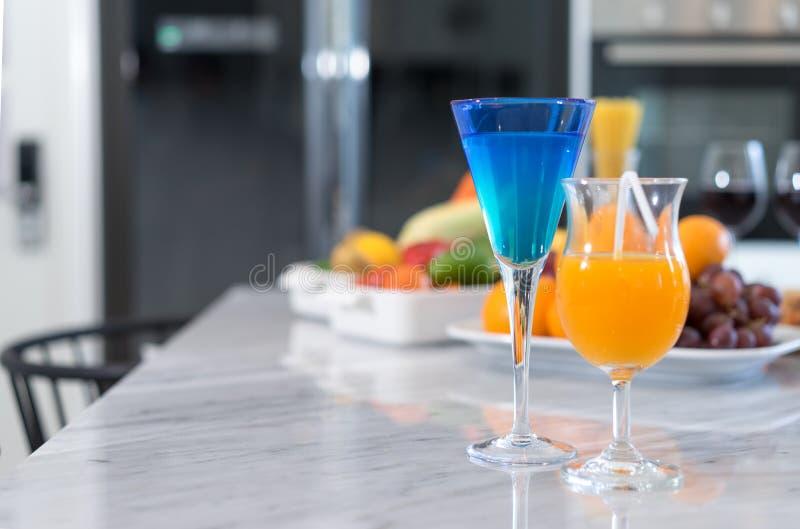 Koktajl i sok pomarańczowy w szkle przy kuchennym pokojem obrazy stock